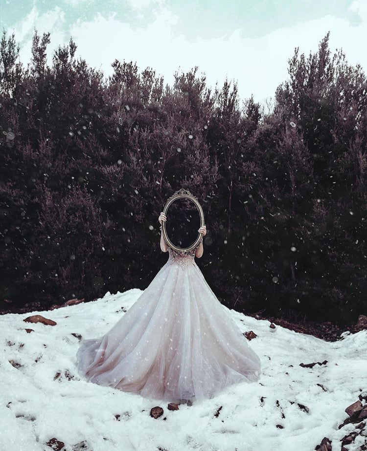 Woman standing in the snow wearing a pink wedding gown holding a mirror up in front of her face