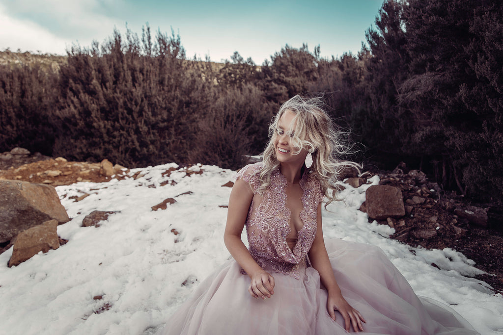 Woman in a pink wedding gown sitting in the snow