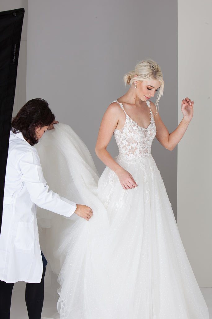 Fashion designer in a white coat helping a model in a wedding gown get into position to pose