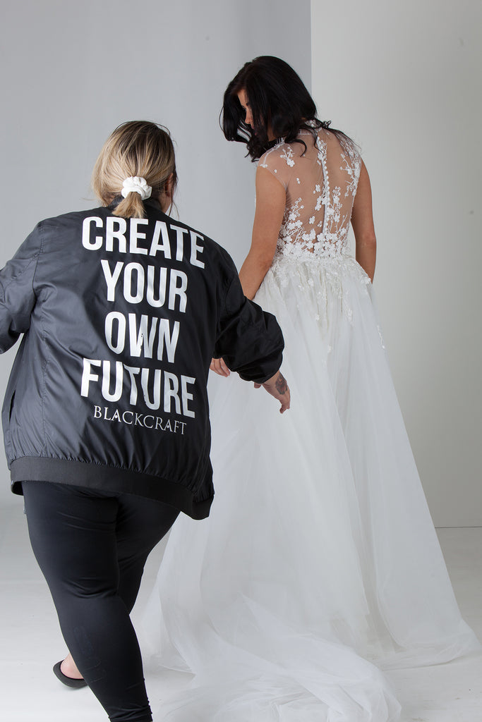 Fashion designer in a black jacket helping a model with her white wedding gown