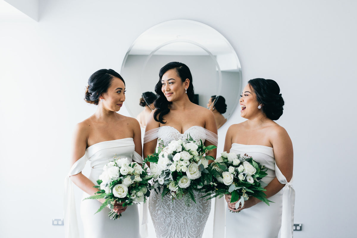 Bride in wedding dress with bridesmaids smiling on the morning of wedding