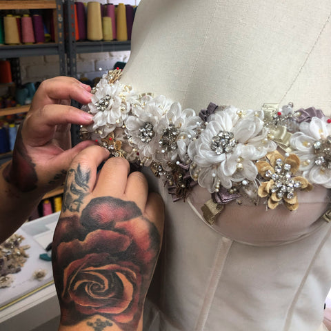 bridal designer with tattooed hands alters wedding dress on dressform