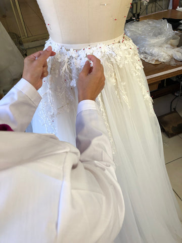bridal designer hand finishing a lace wedding dress