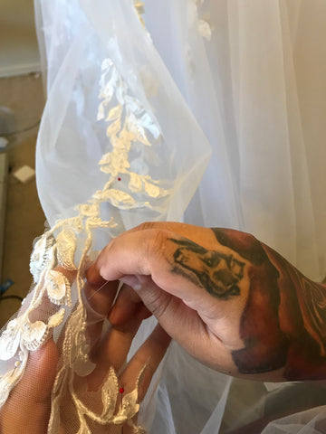 fashion designers tattooed hands placing lace on wedding gown