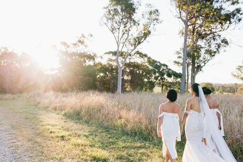 bride and bridesmaids walking through field of grass and trees into the sunset