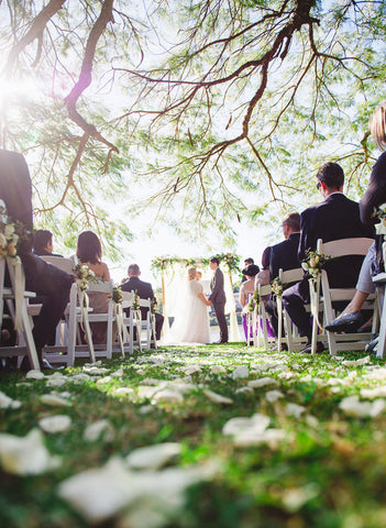 bride and groom exchange vows surrounded by family down grassy aisle on wedding day
