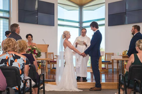 bride and groom having hand fasting wedding ceremony with people looking on at Brisbane church