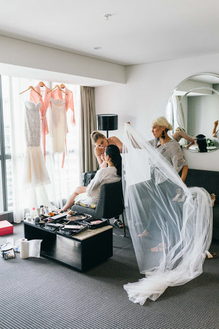 bride having makeup applied while veil and train are being fitted on morning of wedding