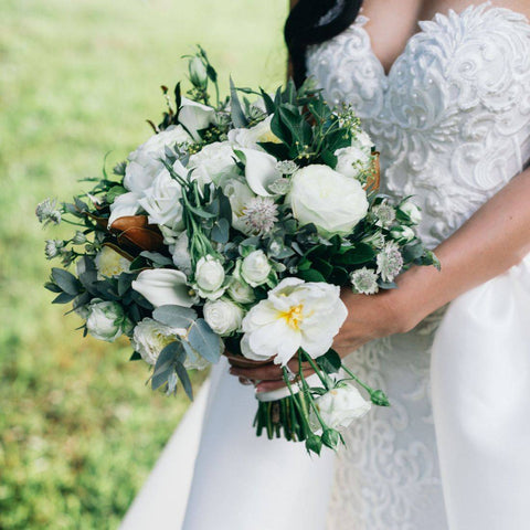 Bride in custom wedding dress holding bouquet of flowers on wedding day