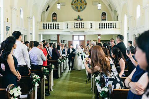bride walking down aisle at church wedding surrounded by family looking on