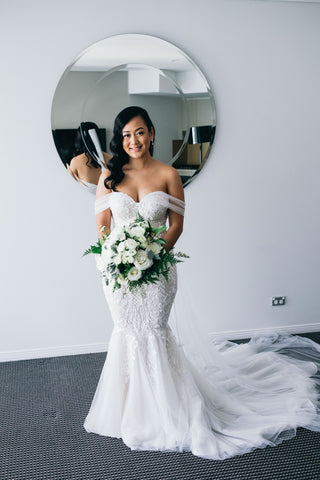 bride wearing wedding dress posing while holding bridal bouquet