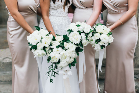 bride with bridesmaids in dresses with bouquets