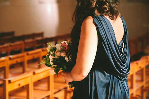 Bridesmaid at church wedding in bridesmaid dress holding bouquet of flowers