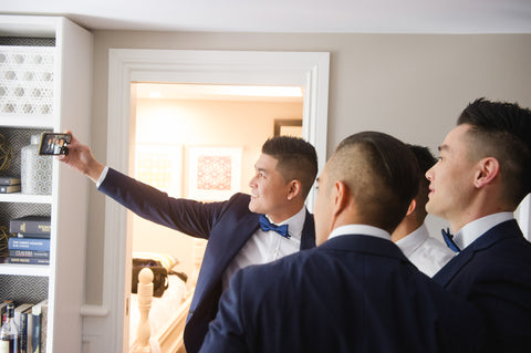groomsmen taking selfie on wedding day