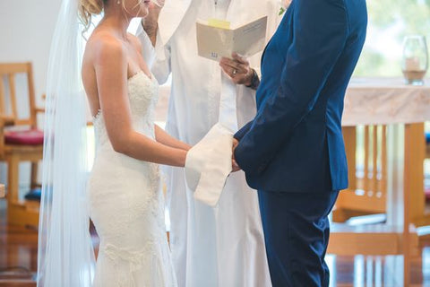 handfasting wedding ceremony carried out by priest with bride in wedding gown and groom in tuxedo
