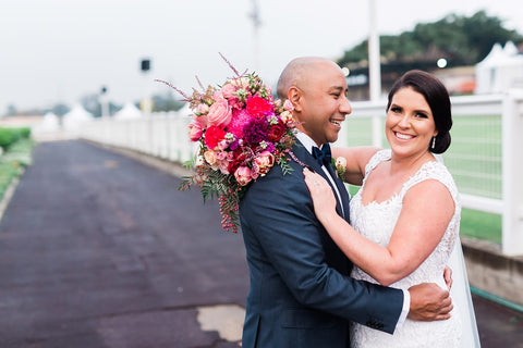 Man in suit with woman wearing wedding dress holding bouquet at eagle farm racecourse