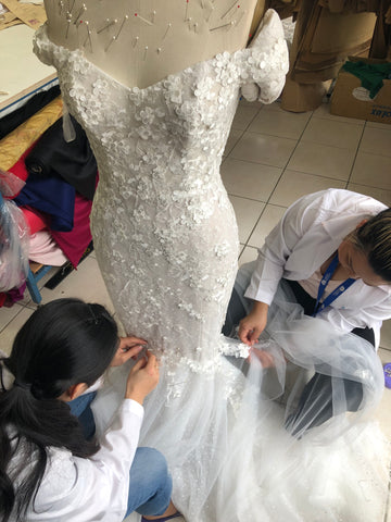 seamstresses work on wedding dress by hand