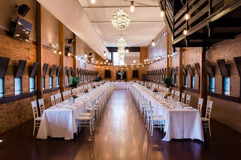 wedding ceremony hall with tables chairs and decor at Eagle Farm Racecourse