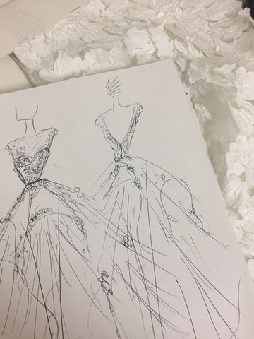wedding dress sketches on table with fabric
