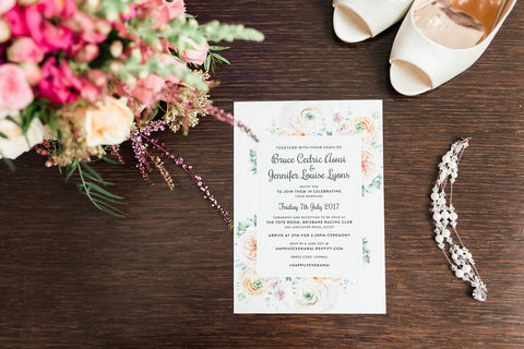 wedding invitations on table with bridal bouquet and wedding heels