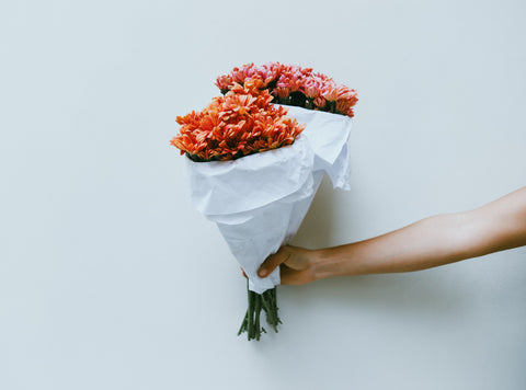 woman holding bouquet of wedding flowers against white wall