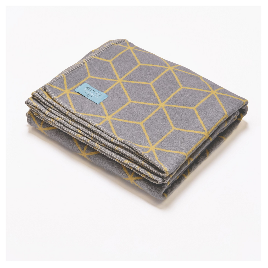grey throw with yellow geometric pattern