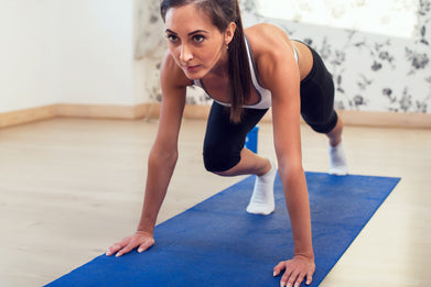 Woman exercising on a floor mat at home