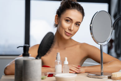Beautiful woman looking in a mirror seated at a makeup counter