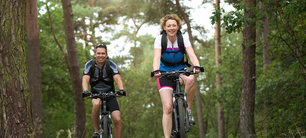 Healthy and happy husband and wife biking outside in nature