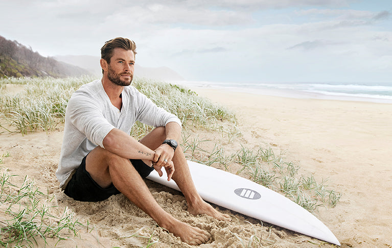 Swisse Global ambassador Chris Hemsworth sitting on beach in Australia with surfboard