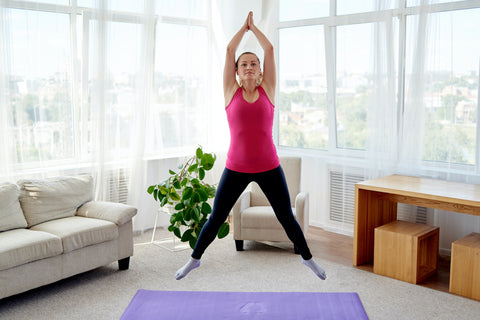 Woman doing jumping jacks to kick-start her energy level first thing in the morning