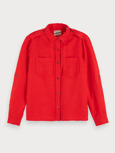 Crafted from soft tencel, this red workwear-inspired shirt features chest pockets, a snap button closure, and sleeve collectors that allow for easy style switch-ups.  By Maison Scotch