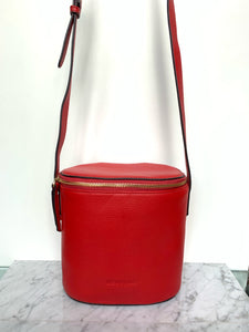 The Morning cross over bag is practical with its inside zipped pocket and adjustable strap yet stylish with its red grain leather and unusual shape.  Dimension: 18 x 19 x 10,5 cm.  Modern simplicity at its best.  By Neuville.