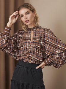 Rich brown blouse with black, white and lilac chequered design. Stylish details added to the voluminous shape with lilac lurex stripe at rib cuff and elastic neck and single button closure at neck.