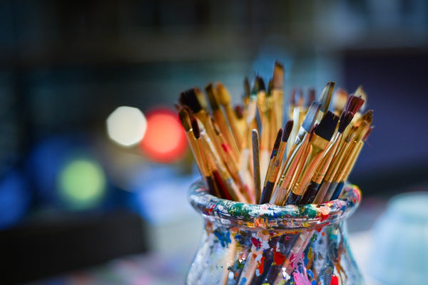 A group of painter's brushes in a bowl