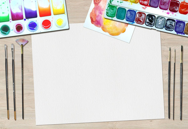 A Photo of an artist sheet of a paper water colors brushes on a desk