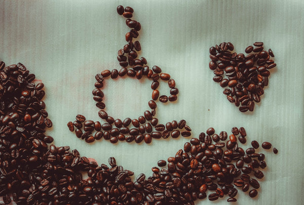 A close up photo of coffee beans used to create art shapes