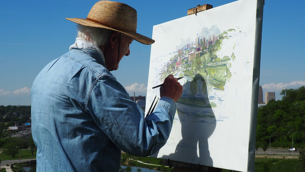 A daylight photo of a man painting on a white paper