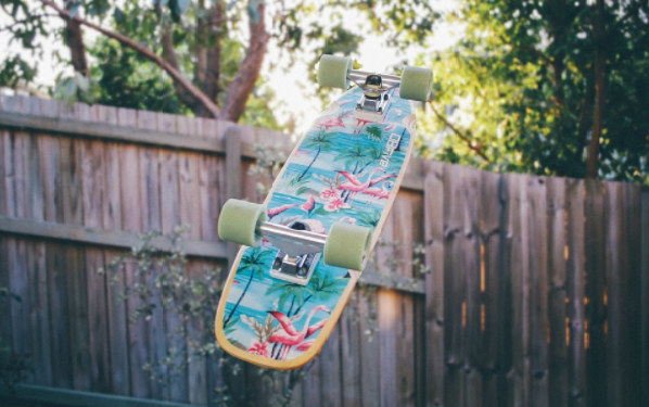 A daylight photo of a skateboard taken in mid air