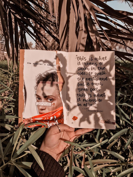 A daylight photo taken of a book held in a hand of a lady and some writings close to a palm tree
