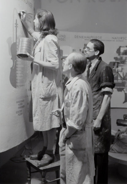 A greyscale photo of two men and a lady preparing for an exhibition