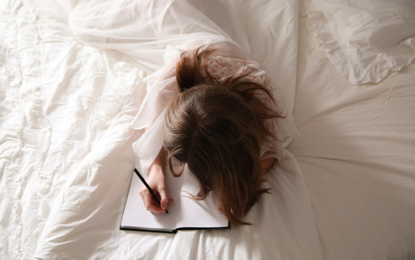 A lady wrapped in a white cloth writing on book on a bed