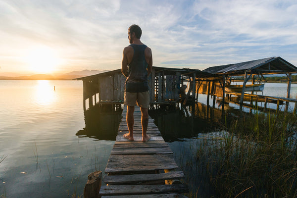 A man in a vest and short standing on a wooden bridge in the sunset