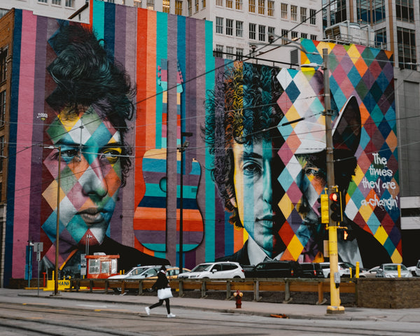 A painting of three rock stars on the street of Minneapolis