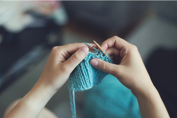 A photo a girl knitting with blue wool