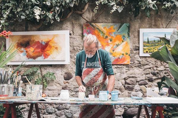 A photo of a Male artist working on a painting in front of other finished painting
