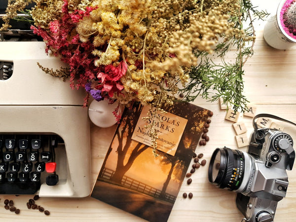 A photo of a bunch of flowers and book arranged on wooden table with vintage typewriter and camera