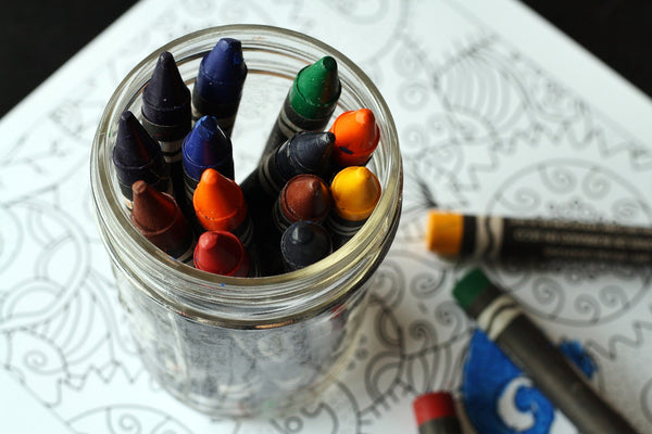 A photo of a different colors of crayons in a glass jar