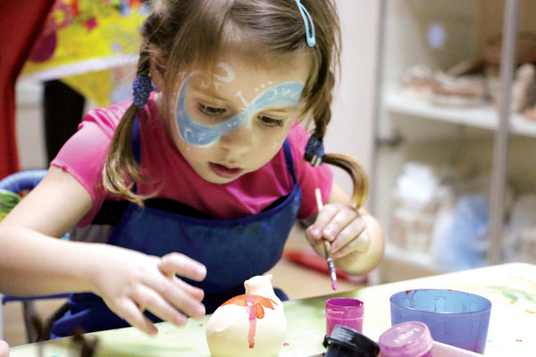 A photo of a girl in pink and blue painting