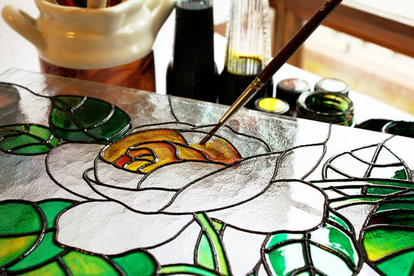 A photo of a glass painting of green and yellow leaves placed on a table
